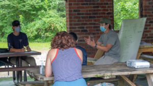 Dr. McGarvey lectures in pop-up classroom at park pavilion